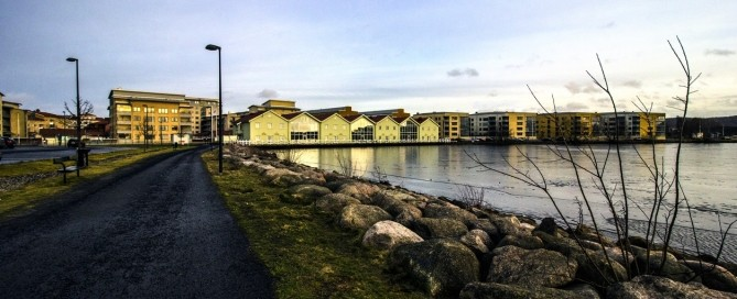 Stylish photo of buildings near a lake in the city of Jönköping, Sweden captured early in the spring of 2016. The ice on the lake has not melted yet.